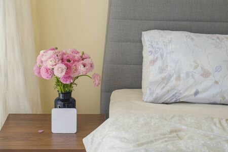 Good morning concept. Empty unmade bed with ranunculus flowers. Close up shot of beautiful spring bouquet in bedroom interior. Copy space, background.