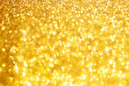 Golden sparkle glitters with bokeh effect and selectieve focus. Festive background with bright gold lights, champagne bubble. Christmas mood concept. Copy space, close up, texture, top view. Banque d'images