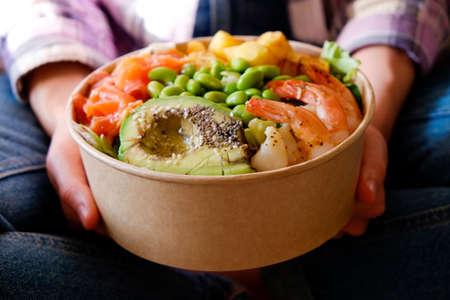 Clean eating diet concept. Vegeterian seafood bowl with smoked salmon, shrimp, avocado in take out paper container in hands of woman having a lunch break. Close up, copy space, top view, background.