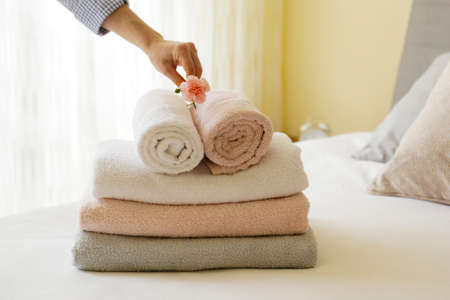House keeping lady changing the set of folded and stacked towels in hotel room with freshly made bed, perfectly clean and ironed sheets in natural sun light. Close up, copy space for text.