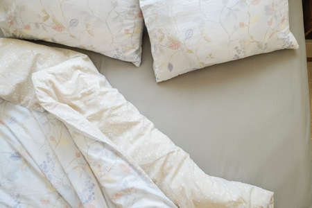 Top view shot of an unmade bed in a hotel room with ironed grey sheets, white blanket and two pillows in natural morning light. Close up, copy space, background. 스톡 콘텐츠
