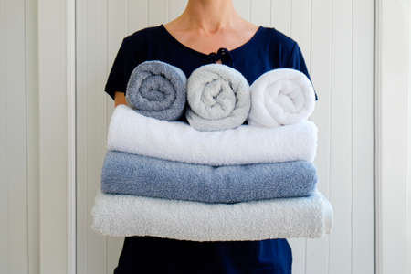 Housekeeping lady holding the set of folded and stacked towels. Room service woman holding a fresh clean laundry. Close up, copy space for text, background.