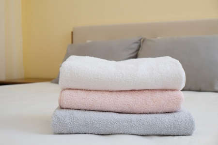 Hotel room with freshly made bed, perfectly clean and ironed sheets, stack of new folded towels in natural sun light. Close up, copy space for text.