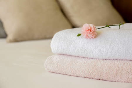 Hotel room with freshly made bed, perfectly clean and ironed sheets, stack of new folded towels and single flower as decoration in natural sun light. Close up, copy space for text.