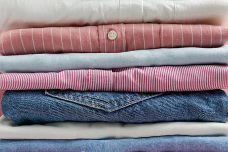 Cropped image with stack of colorful perfectly folded clothing items. Macro shot of pile of different pastel color shirts, sweaters & pants. Close up, copy space, background. Reklamní fotografie