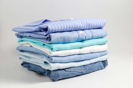Stack of colorful perfectly folded clothing items. Pile of different pastel color shirts, sweaters isolated and other garments on white background. Close up, copy space. 스톡 콘텐츠