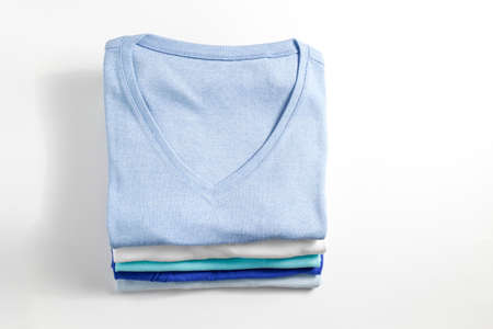 Stack of colorful perfectly folded clothing items. Pile of different pastel color shirts and sweaters isolated on white background. Close up, top view, copy space.