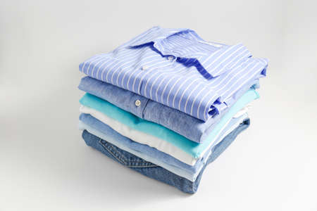 Stack of colorful perfectly folded clothing items. Pile of different pastel color shirts, sweaters isolated and other garments on white background. Close up, top view, copy space.