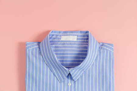 One perfectly folded buttoned shirt with striped pattern. Single piece of formal wear with blank label isolated on pink background. Close up, top view, copy space.