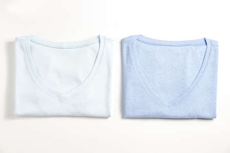 Two perfectly folded clothing items. Couple different cool colored v-neck t-shirts isolated on white background. Close up, top view, copy space.
