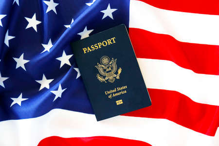 Latest version of United States of America citizen Passport with biometric ID chip on USA national flag. Person identification document. Close up, copy space, background, top view, flat lay. Standard-Bild