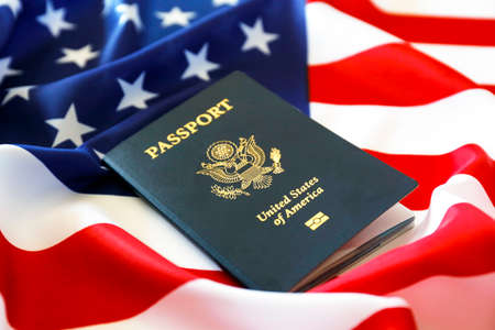 Latest version of United States of America citizen Passport with biometric ID chip on USA national flag. Person identification document. Close up, copy space, background, top view, flat lay. Stock Photo