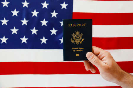 Macro shot of man's hand holding the latest version of United States of America citizen Passport with biometric ID chip. Person identification document. Close up, copy space, USA flag background.
