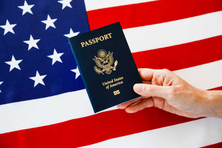 Macro shot of woman's hand holding the latest version of United States of America citizen Passport with biometric ID chip. Person identification document. Close up, copy space, USA flag background.