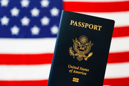 Latest version of United States of America citizen Passport with biometric ID chip standing on table with USA flag on background. Person identification document. Close up, copy space. 스톡 콘텐츠