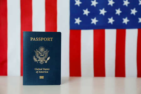 Latest version of United States of America citizen Passport with biometric ID chip standing on table with USA flag on background. Person identification document on display. Close up, copy space.