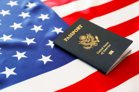 Latest version of United States of America citizen Passport with biometric ID chip on USA national flag. Person identification document. Close up, copy space, background, top view, flat lay.