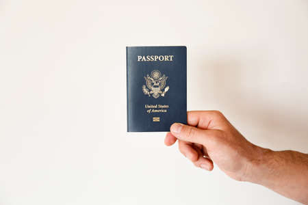 Macro shot of man's hand holding the latest version of United States of America citizen Passport with biometric ID chip. Person identification document. Close up, copy space, white wall background.