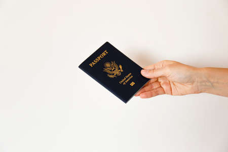 Macro shot of woman's hand holding the latest version of United States of America citizen Passport with biometric ID chip. Person identification document. Close up, copy space, white wall background. 스톡 콘텐츠