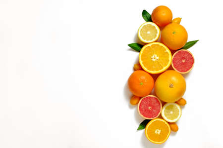 Close up image of juicy organic whole and halved assorted citrus fruits, green leaves & visible core texture, isolated white background, copy space. Vitamin C loaded food concept. Top view, flat lay. Stock Photo
