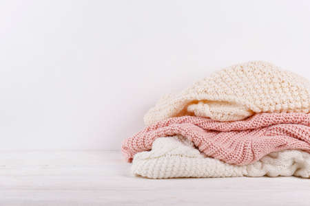 Bunch of knitted warm pastel color sweaters with different knitting patterns stacked in messy pile on white wooden table, blank wall background. Fall winter season knitwear. Close up, copy space.