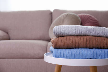 Stack of clean freshly laundered, neatly folded women's clothes on the table. Pile of shirts, dresses and sweaters on the table, concrete wall background. Copy space, close up, top view.