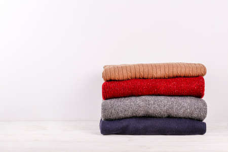 Stack of colorful perfectly folded sweaters on white wood texture table. Pile of different pastel color shirts and sweaters on wooden table, white wall background. Close up, top view, copy space. Stok Fotoğraf