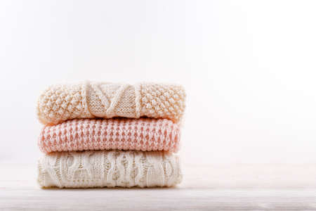 Bunch of knitted warm pastel color sweaters with different knitting patterns folded in stack on white wooden table, white wall background. Fall winter season knitwear. Close up, copy space for text 스톡 콘텐츠 - 158606869