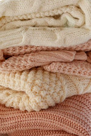 Bunch of knitted warm pastel color sweaters with different knitting patterns folded in stack, clearly visible texture. Stylish fall / winter season knitwear clothing. Close up, copy space for text. 스톡 콘텐츠 - 158607182