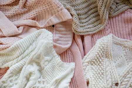 Bunch of knitted warm pastel color sweaters with different knitting patterns laid in messy pile, clearly visible texture. Stylish fall / winter season knitwear clothing. Close up, copy space for text.