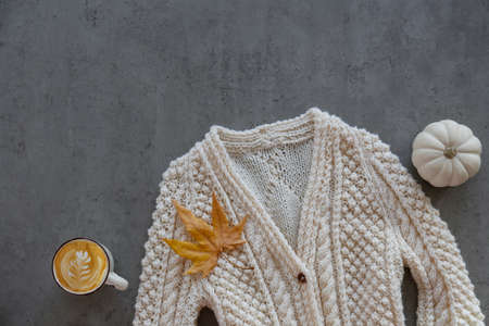 Oversized knitted cardigan sweater with vintage buttons, pumpkin and yellow maple leaf, autumnal symbols. Background, top view, close up, copy space, flat lay.