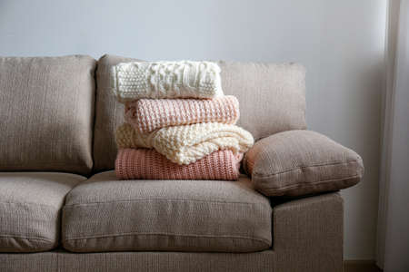 Stack of clean freshly laundered, neatly folded women's clothes on brown textile couch. Pile of shirts and sweaters on the sofa. Copy space, close up, top view, background.