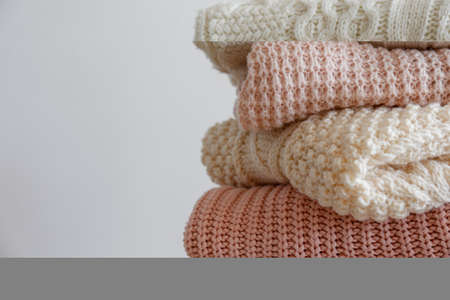 Bunch of knitted warm pastel color sweaters with different knitting patterns folded in stack, clearly visible texture. Stylish fall / winter season knitwear clothing. Close up, copy space for text.