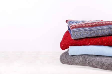 Bunch of colorful sweaters with different patterns stacked in messy pile on white wooden table, blank wall background. Fall winter season knitwear. Close up, copy space.