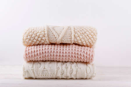 Bunch of knitted warm pastel color sweaters with different knitting patterns folded in stack on white wooden table, white wall background. Fall winter season knitwear. Close up, copy space for text