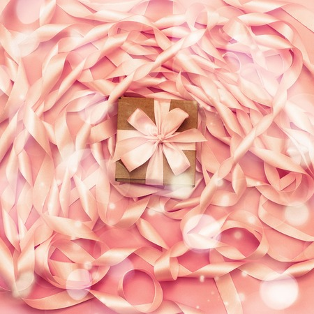 Boxes with gifts on the background of a Coil of decorative satin ribbons of pink color. Material for creativity of Fashion Design. Festive decoration