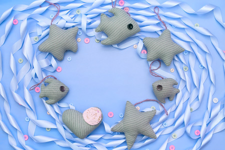 Textile toy heart and star on a festive background of satin ribbon. Decorative buttons top view Фото со стока