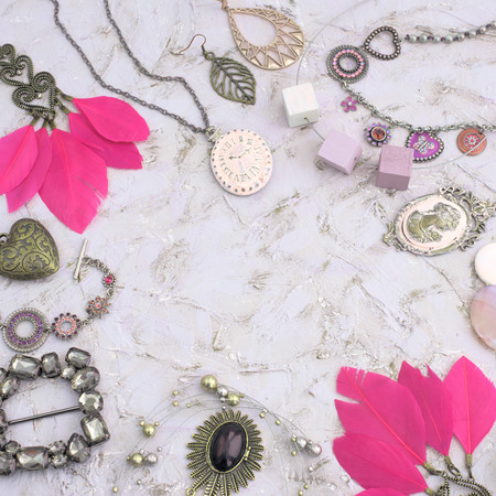 Set vintage jewelry for women. Decorative composition frame, necklace, bracelet, locket, necklaces, earrings with feathers. Top view flat lay