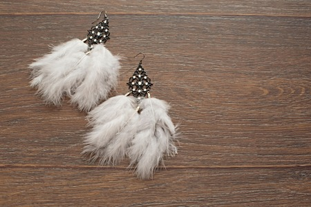 Beautiful delicate earrings with feathers on a wooden background. The view from the top. The concept of fashion and design