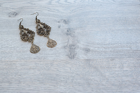 Vintage long earrings made of metal on wooden background. Top view flat lay