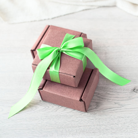 Decorative box for the holiday. Gifts beautifully packaged in boxes and tied with satin ribbon. Wood background flat lay