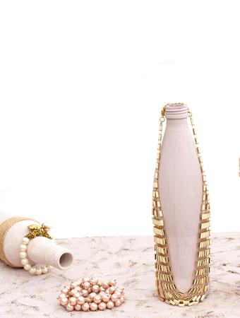 Bottle for home decoration on textured background. Paint, decor twine. Women's jewellery, necklace, bracelet.