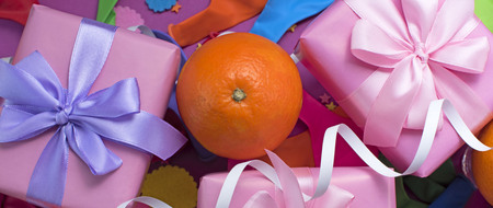 Banner Decorative composition Three boxes with gifts Satin ribbon Bow Oranges Confetti Serpentine birthday party. The view from the top