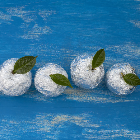Three apples wrapped in foil are natural green leaves. Wooden candy blue background. Flat lay top view Kho ảnh