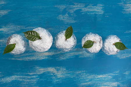 Five apples in the shell foil with natural green leaves. Wooden candy blue background. Flat lay top view