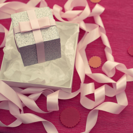 Festive composition with gift box on a bright pink background. Decoration satin ribbon bow. Textured background Stock Photo