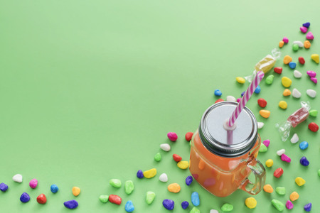 Natural Fresh Smoothies Drink in glass Cup with straw on green background. Candy colored sweets. Flat lay top view