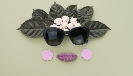 Surrealism Banner Background for text, the imitation of facial concept. Sunglasses natural leaves and white flowers on a green background. Flat lay top view