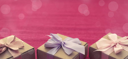 Banner Festive composition three Kraft boxes with gifts on bright pink background. Decoration satin ribbon bow. Textured background