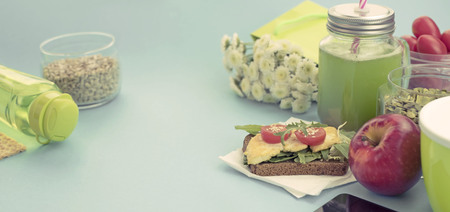 Banner Healthy vegetarian Breakfast Sandwich grain bread tofu cheese, detox smoothie, pumpkin seeds, cherry tomatoes, natural flowers, blue background, notebook, Lunch box soup for lunch. Stock Photo